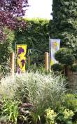colourful banners hung in garden in front of trees and behind tall grasses