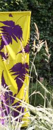 Garden textile banner, purple fern pattern design on yellow background, in front of grasses.