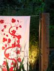 White textile screen with curvy red vine printed plant design hung on modular hanging system lit up at night in a garden